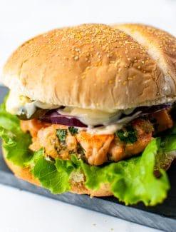 salmon burger with lettuce and tartar sauce on a bun