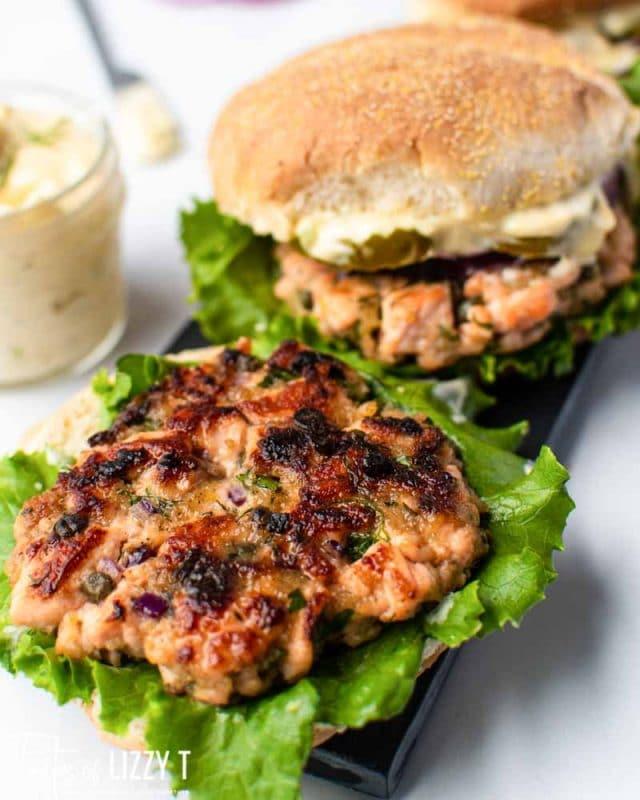 golden brown salmon burgers on lettuce
