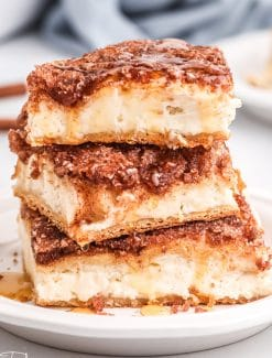 stack of three sopapilla cheesecake bars with honey