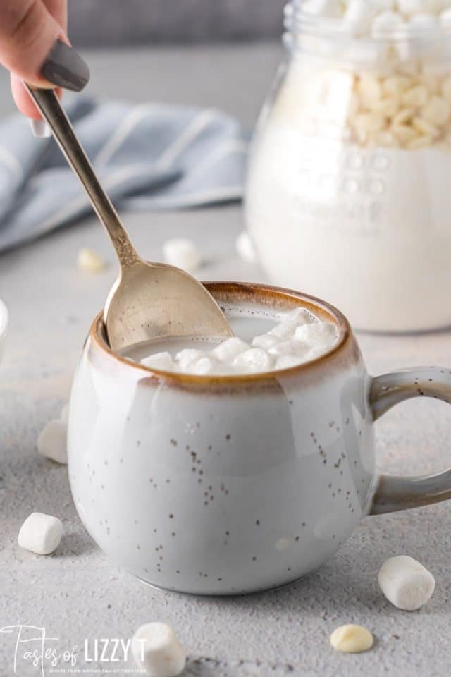mug of white hot chocolate with spoon stirring