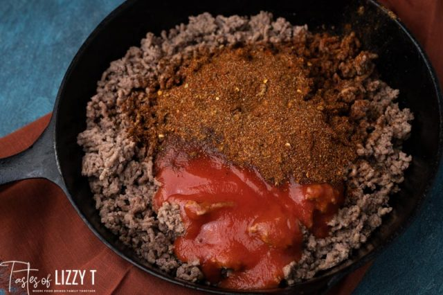 taco meat in a skillet with seasoning and sauce