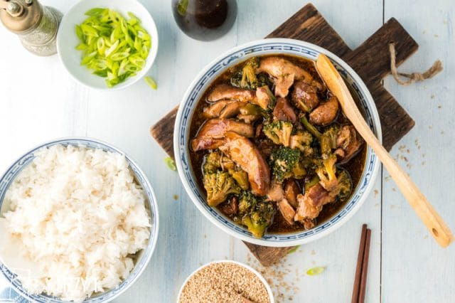 table with bowls of rice, chicken and broccoli