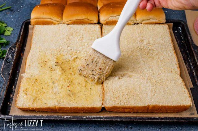 brushing butter over sliced rolls