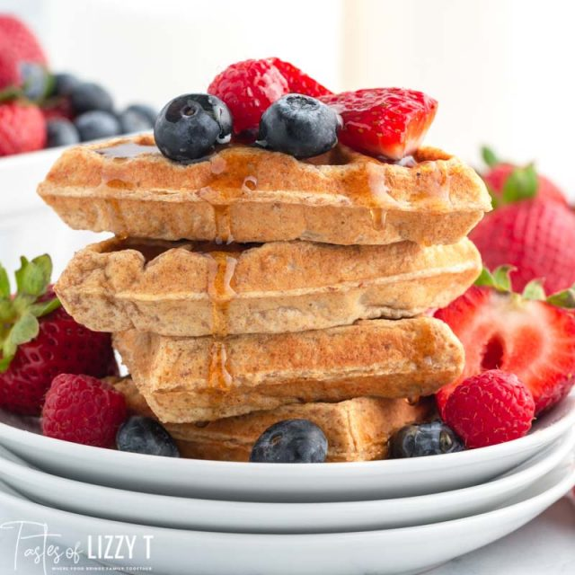 a stack of 4 whole grain waffles with berries and syrup