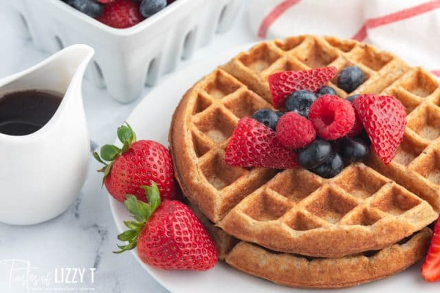 two whole grain waffles on a plate with fresh berries