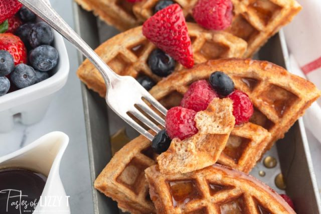 a piece of waffle and berries on a fork