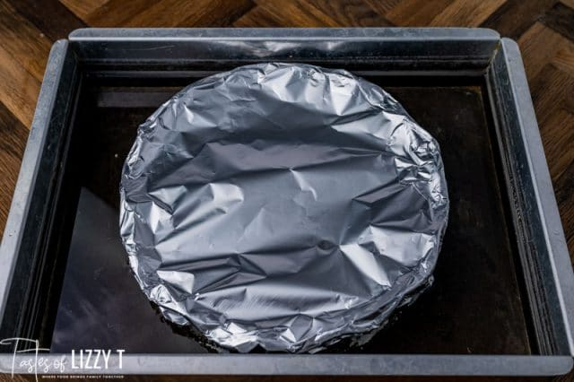 a pie plate covered in foil in a pan