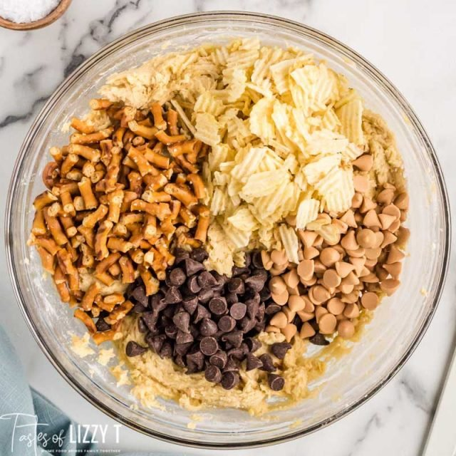 a bowl of cookie dough with chips, pretzels, butterscotch and chocolate chips