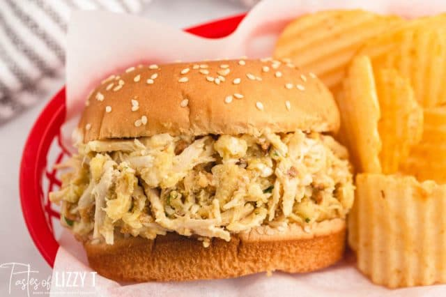 a shredded chicken sandwich in a basket with chips
