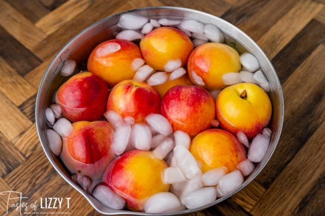 whole peaches in a bowl of ice water