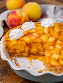 a peach pie on a table with one slice missing
