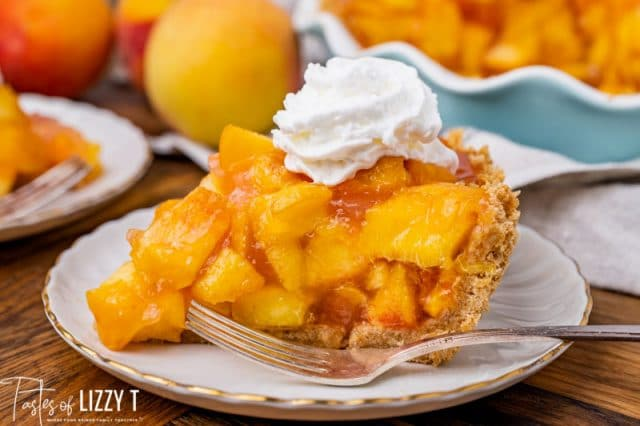 a piece of pie with fresh peaches and whipped cream