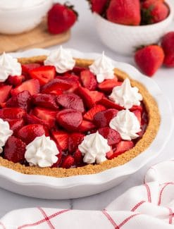 strawberry pie with whipped cream on a table