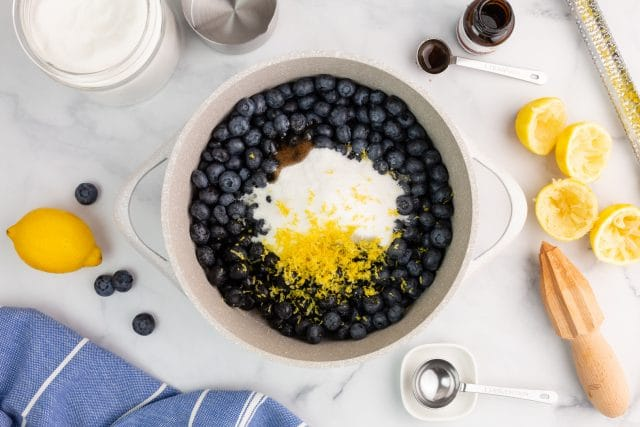 ingredients for blueberry jam in a saucepan