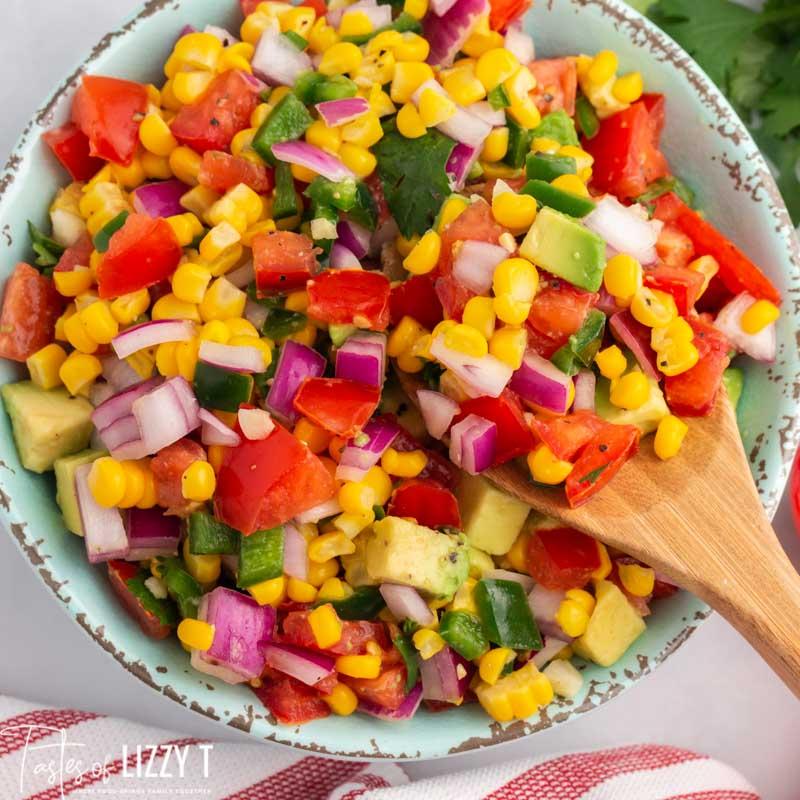 bowl of corn tomato avocado salsa with a spoon