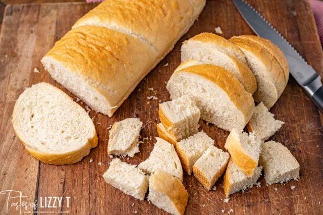 French bread cut in cubes on a cutting board