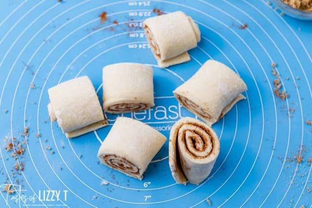 cut cinnamon rolls on a baking mat