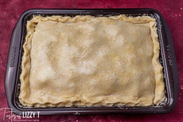 unbaked apple pie in a baking pan
