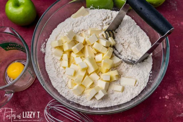 butter over flour in a bowl with a pastry cutter