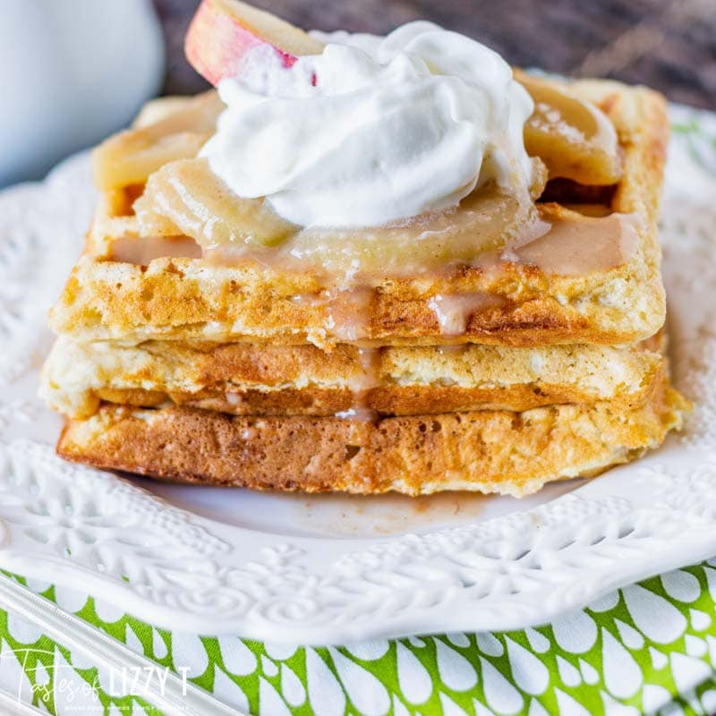 three waffles on a plate with apple slices and cinnamon syrup