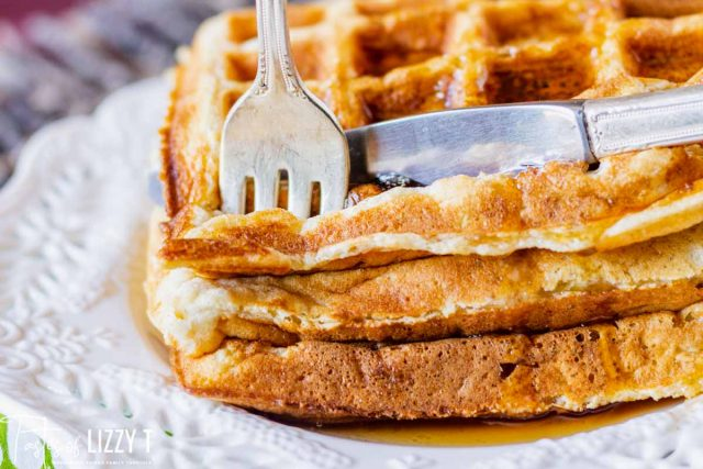 a knife and fork cutting into a stack of waffles