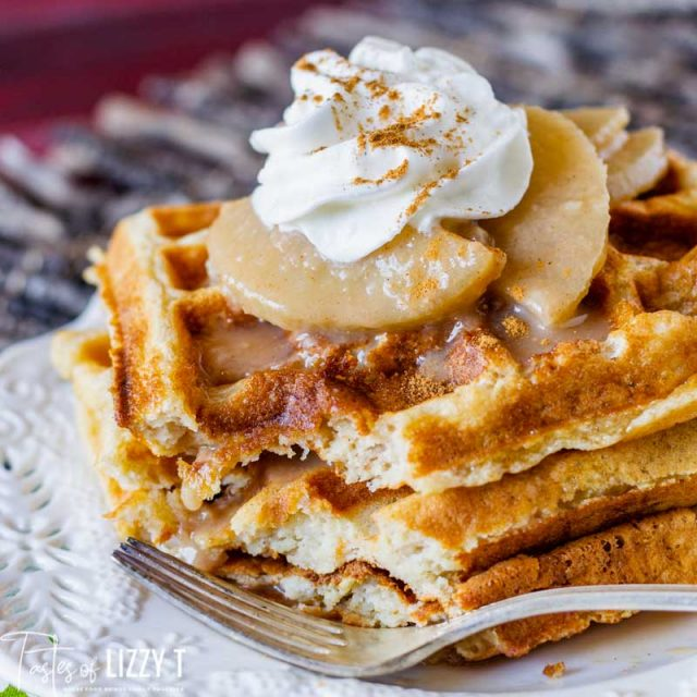three waffles sitting on a plate with apples and whipped cream