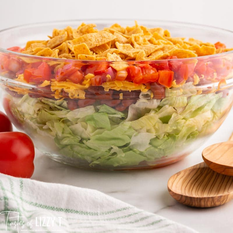 a layered taco salad in a glass bowl