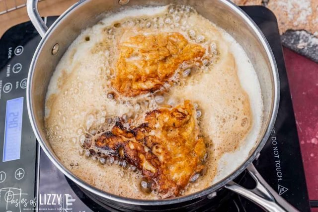 chicken frying in butter in a skillet