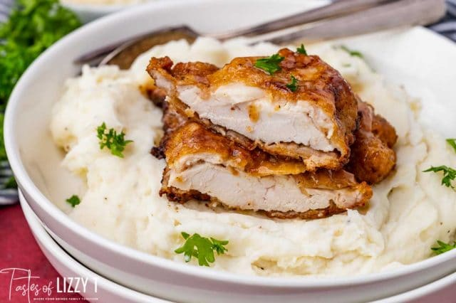 fried chicken breast cut in half over mashed potatoes