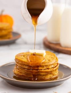 syrup pouring over a stack of pancakes