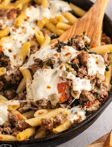 fresh mozzarella over italian sausage and pasta in a skillet