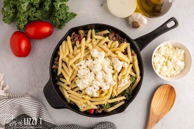fresh mozzarella over pasta in a skillet